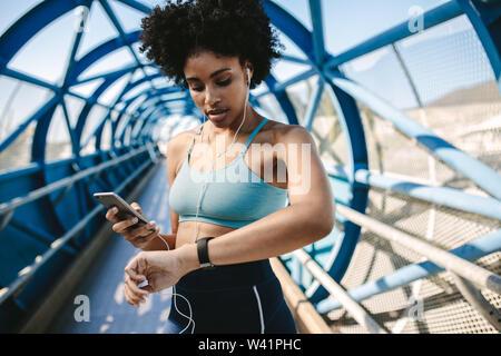 De la sportive à la smart à regarder et holding smart phone dans son autre main, à l'extérieur. Femme Fitness la configuration de son smart watch pour son exécution. Banque D'Images