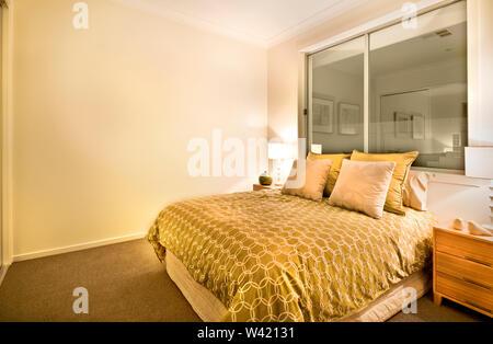 Intérieur chambre à coucher moderne dans un luxueux appartement avec un lit king size, la levée de l'oreiller et une couverture jaune à côté de la fenêtre en verre, la salle est illu Banque D'Images