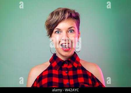 Les gens et les émotions - jeune femme avec de courts cheveux noirs montre sa langue Banque D'Images