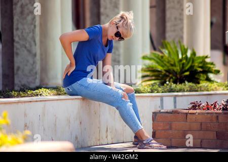 Les maux de dos, jeune femme a une lésion musculaire pendant la marche en plein air. La santé, la médecine et les gens concept Banque D'Images