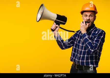 L'homme travailleur en colère en orange casque avec un mégaphone sur fond jaune - image