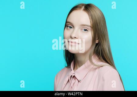 Portrait d'une jeune fille souriante sur fond bleu - image Banque D'Images