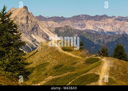 SAUZE D'Oulx, ITALIE - Le 7 août 2010. Un homme monte un VTT le long d'un sentier de crête avec de hauts sommets alpins dans l'arrière-plan Banque D'Images