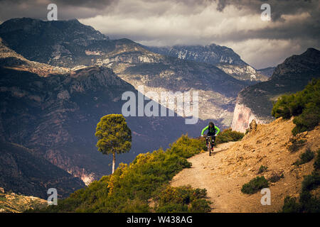 Un homme monte un vtt sur une piste de terre isolée dans les montagnes de l'Atlas. De hautes montagnes et rainclouds en arrière-plan. Banque D'Images