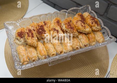 Les tartes à la viande, le chou ou tout remplissage. Tartes cuites au four. Sur une assiette blanche et un fond de couleur pêche. Tartes fraîches avec de la viande, le chou ou de toute fi Banque D'Images