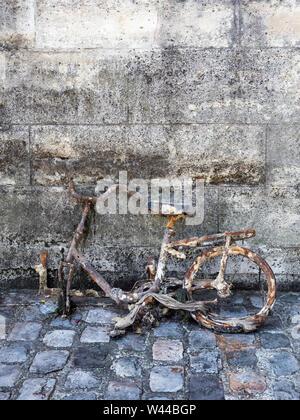 Un rouillé, cassé, sale et délabrée location s'appuie contre un mur endommagé par l'eau et de la mousse sur une rue pavée humide à proximité d'une rivière Banque D'Images