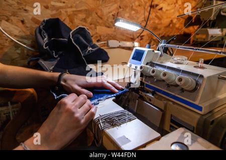 Mains d'une jeune couturière sont vus de l'exploitation d'un overlocking machine en atelier. Bords de tissu denim bleu sont sertis sur machine industrielle par le travail Banque D'Images