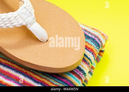 Les femmes de couleur naturel tressé de cause à jour de plage Tongs et plié les serviettes de plage à rayures colorées sur fond jaune vif. Banque D'Images