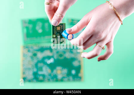 La femme est technicien en fixant un condensateur sur le circuit imprimé. Le concept de l'ordinateur, le service, l'électronique, le matériel, la réparation, la mise à niveau d'un