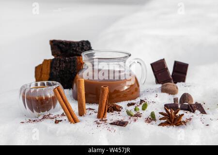 Un pichet de thé chai chaga fraîchement préparé est vu dans la neige, avec des ingrédients de la cannelle, l'anis étoilé et de chocolat noir, un verre canadien aromatiques