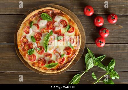 Pizza Margherita sur une planche à découper, les tomates fraîches et basilic sur table en bois, vue du dessus Banque D'Images