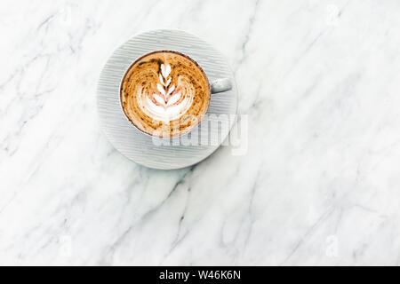 Tasse de café frais cappuccino avec classic latte art et chocolat sur fond de marbre blanc à la mode table. Lieu vide pour le texte, copiez l'espace. Le café Banque D'Images