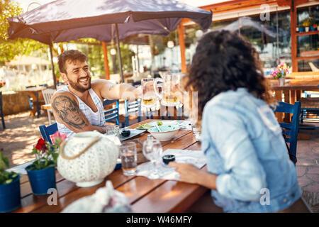 Beau couple d'amoureux assis dans un restaurant bénéficiant dans la bière et la conversation