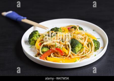 Asia food. Les nouilles Udon aux légumes sur le fond noir, cuit sauté au wok Banque D'Images