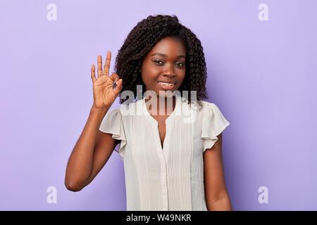 Joli sourire femme afro avec les cheveux bouclés ondulés businesswoman making ok signe, tout est ok. Le langage du corps