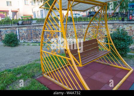 Parc de la ville en été, vide balançoire en bois avec cadre en métal décoratif jaune, mobilier de loisirs de plein air Banque D'Images