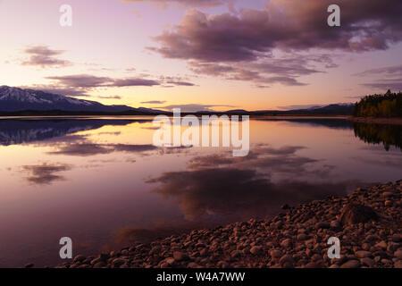 Les belles couleurs douces de coucher du soleil se reflètent dans un lac du Grand Tetons National Park.