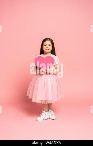 Mode rire petite fille à tulle dress holding papier rouge coeur et souriant à la caméra isolé sur fond rose. Banque D'Images