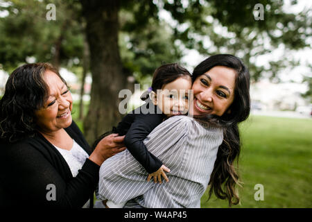 Grand-mère, mère et fille hugging and laughing in park