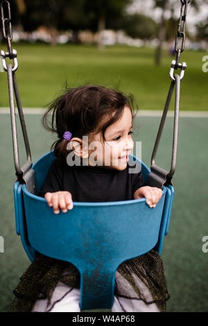 Little girl sitting in swing smiling Banque D'Images