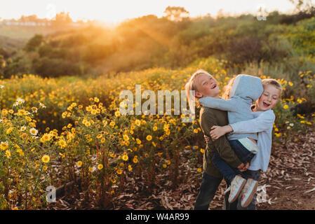 Frères et sœurs hugging au coucher du soleil dans le champ de fleurs Banque D'Images