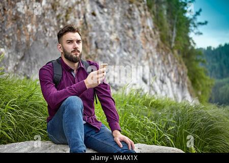 Un jeune homme barbu de blancs ethnos est titulaire d'un smartphone dans ses mains, au cours d'aventures sur un sentier de randonnée, il se repose assis sur une pierre dans l'ecosy