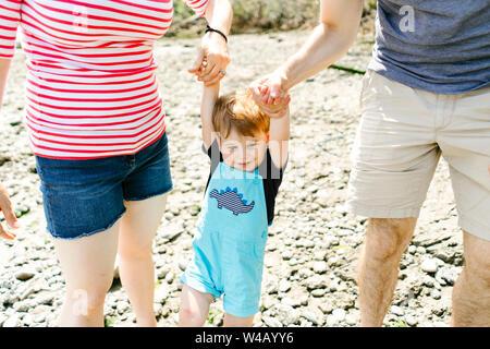 Libre d'un jeune bébé garçon tenant la main avec ses parents