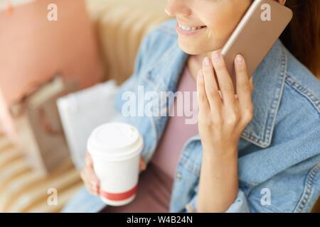 Young smiling woman with coffee cup parlant au téléphone tout en restant assis sur le banc en commercial couvert par les sacs Banque D'Images