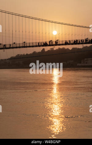 Belle vue sur l'eau du Gange et Ram Jhula bridge au coucher du soleil. Rishikesh, Inde Banque D'Images