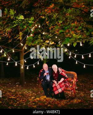Happy senior couple boire du thé le soir assis sur le canapé Banque D'Images