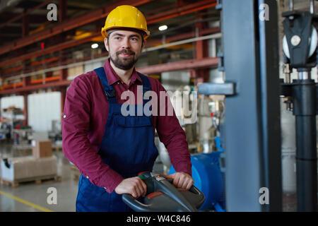Ingénieur au casque de travailler avec l'équipement mécanique à l'établissement industriel. Banque D'Images