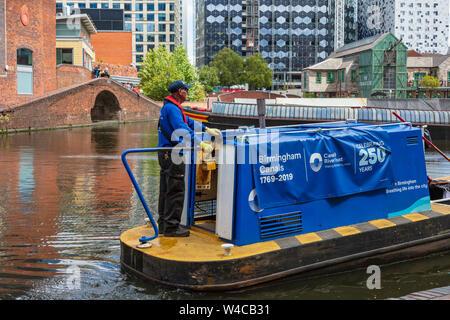 Un travailleur confiance Canal steers une barge sur le gaz naturel du bassin de la rue sur la nouvelle ligne principal canal dans le centre de Birmingham, UK Banque D'Images