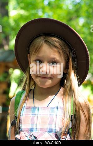 Fille blonde dans un chapeau avec cheveux longs promenades à travers le parc avec un sac à dos sur ses épaules et mange une pomme sur un jour d'été ensoleillé