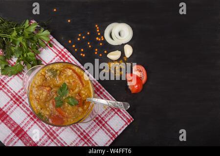 Soupe aux lentilles rouges avec tomates, oignons, l'ail et les épices dans un bol en verre avec une cuillère debout sur une nappe sur un fond noir. Copier spaes Banque D'Images
