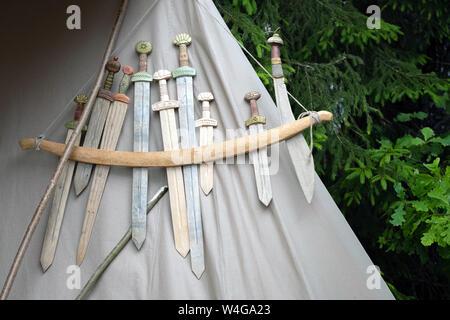 Répliques d'armes médiévales en bois close combat affiché sur la texture de tissu gris Banque D'Images
