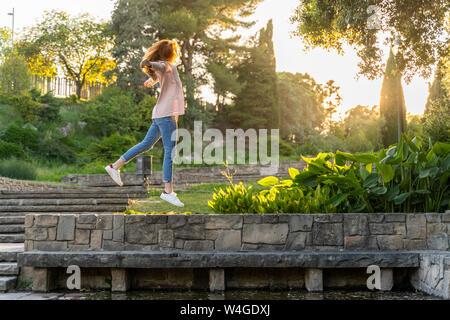 Jeune femme rousse sautant dans un parc
