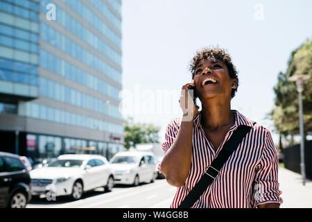 Femme parlant au téléphone tout en marchant dans la ville