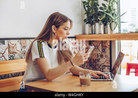 Jeune femme en utilisant le téléphone mobile et l'ordinateur portable en cafe