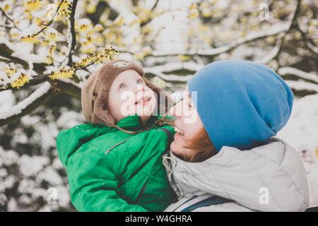 Portrait de petit garçon apprécie sa première neige sur les bras de sa mère