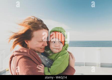 Bébé garçon mère portant en écharpe sur un ferry Banque D'Images