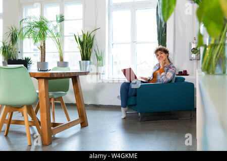 Smiling woman using laptop in armchair in office