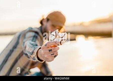 Man's hand holding tatoué mordu donut au coucher du soleil, close-up