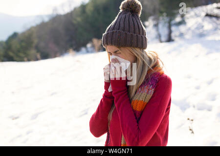 Young blonde woman blowing nose en hiver Banque D'Images