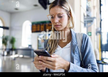 Jeune femme textos avec son téléphone portable dans le hall de la gare
