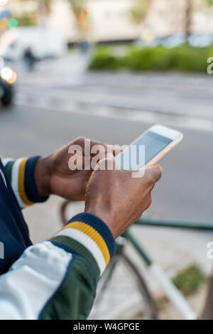 Close-up of man using cell phone in the city Banque D'Images
