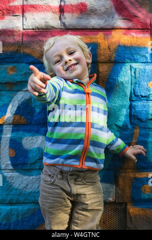 Portrait of smiling little boy standing in front of colorful wall pointant sur quelque chose Banque D'Images