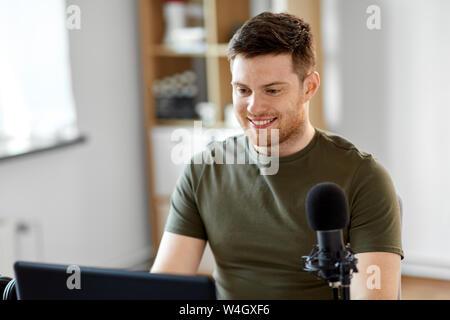 Homme avec portable et le microphone at home office Banque D'Images