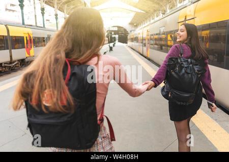 Vue arrière de deux jeunes femmes avec des sacs à main dans la main sur la plate-forme, Porto, Portugal Banque D'Images