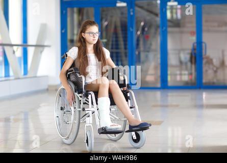 Une jeune fille dans un fauteuil roulant est debout dans le couloir de l'hôpital. Banque D'Images