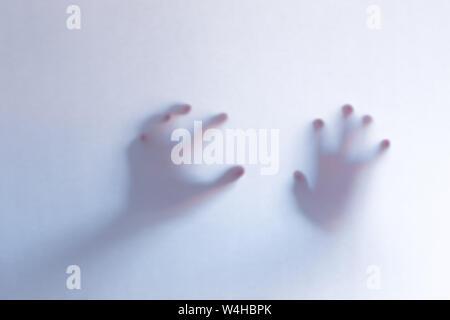 Scary ghost floue les mains derrière un fond en verre blanc. L'orientation horizontale Banque D'Images